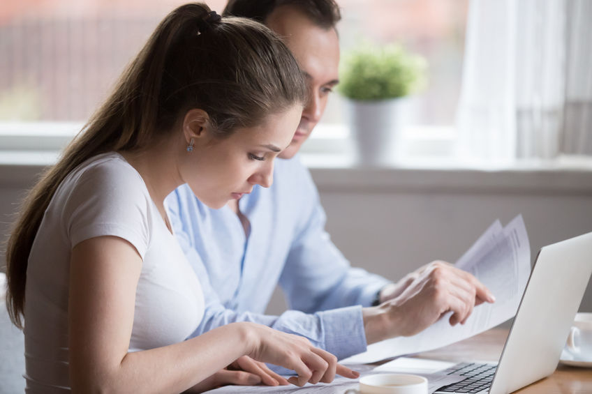 Serious man and woman reading paperwork managing family budget