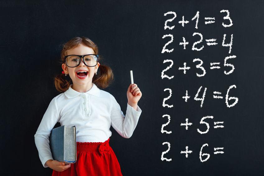 Happy schoolgirl preschool girl with book near school blackboard